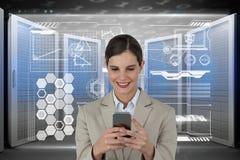 Geschäftsfrau, die ein Telefon und Grafiken im Serverraum hält Lizenzfreie Stockbilder