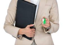Geschäftsfrau, die eine Datei und einen Schlüssel gegen weißen Hintergrund hält Stockfotografie
