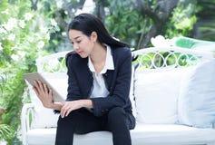 Geschäftsfrau, die eine digitale Tablette in einem Wohnzimmer verwendet Stockbild