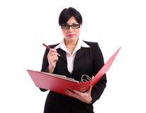 Geschäftsfrau, die eine große rote Datei und eine Feder anhält Stockfotografie