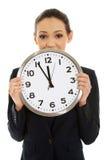 Geschäftsfrau, die eine große Uhr hält Stockfotos