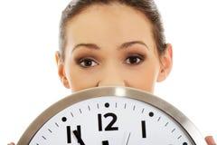 Geschäftsfrau, die eine große Uhr hält Lizenzfreies Stockfoto