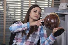 Geschäftsfrau, die eine Kugel hält und einen Platz für ein holida wählt Stockbild