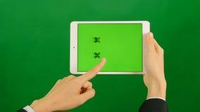 Geschäftsfrau, die eine leere grüne Schirmtablette auf grünem Hintergrund verwendet stock video