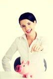 Geschäftsfrau, die eine Münze in eine piggy Querneigung setzt Stockfotografie