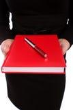 Geschäftsfrau, die eine rote Tagesordnung und eine rote Feder anhält Lizenzfreies Stockfoto