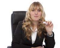 Geschäftsfrau, die eine Süßigkeit an ihrem Schreibtisch isst Stockbild