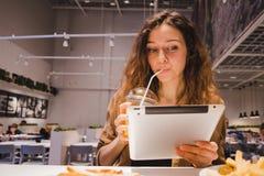 Geschäftsfrau, die eine Tablette betrachtet und Saft von einem Rohr in einem Schnellimbisscafé trinkt stockfotos