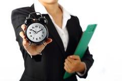 Geschäftsfrau, die eine Timer-Warnung 10 hält 10 morgens lokalisiert auf Weiß Stockfotografie