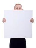 Geschäftsfrau, die eine unbelegte Anschlagtafel anhält Stockbild