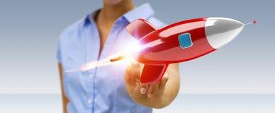 Geschäftsfrau, die eine Wiedergabe der Rakete 3D hält und berührt Lizenzfreies Stockfoto
