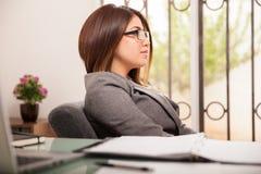 Geschäftsfrau, die in einem Büro sich entspannt Stockfotografie