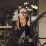 Geschäftsfrau, die einem Geheimnis durch das Telefon sagt Stockfotos