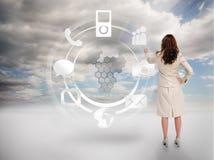 Geschäftsfrau, die an einem Hologramm mit Ikonen sich berührt Lizenzfreies Stockfoto