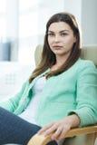 Geschäftsfrau, die in einem Lehnsessel sitzt Stockfotos