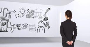 Geschäftsfrau, die in einem Raum 3D mit einer Begriffsgraphik auf der Wand steht Lizenzfreies Stockbild