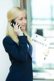 Geschäftsfrau, die an einem Telefon, Lastenhefte verwahrend spricht Lizenzfreie Stockfotos