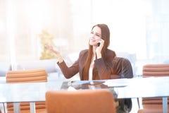 Geschäftsfrau, die an einem Tisch im Büro liest eine Tablette mit einem erfreuten Lächeln sitzt Lizenzfreie Stockfotografie