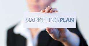 Geschäftsfrau, die einen Aufkleber mit dem Vermarktungsplan geschrieben auf ihn hält Lizenzfreies Stockfoto