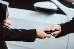 Geschäftsfrau, die einen Autoschlüssel von einem Verkäufer nimmt stockbilder