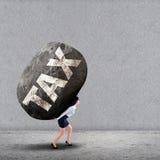 Geschäftsfrau, die einen großen Felsen der STEUER trägt Stockfoto
