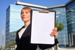 Geschäftsfrau, die einen Leerbeleg vorlegt Lizenzfreies Stockbild