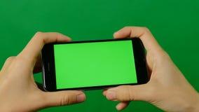 Geschäftsfrau, die einen leeren grünen Schirmhandy auf grünem Hintergrund verwendet stock video