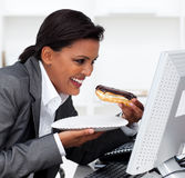Geschäftsfrau, die einen Schokolade Eclair isst Lizenzfreie Stockfotografie
