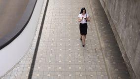Geschäftsfrau, die einen Smartphone geht und verwendet Lizenzfreie Stockfotografie