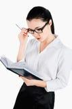 Geschäftsfrau, die einen Stift hält und Tagebuch betrachtet Lokalisiert auf Weiß Lizenzfreies Stockfoto