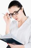 Geschäftsfrau, die einen Stift hält und Tagebuch betrachtet Lokalisiert auf Weiß Lizenzfreies Stockbild