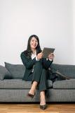 Geschäftsfrau, die einen TabletpC lesend sitzt Lizenzfreie Stockbilder