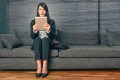 Geschäftsfrau, die einen TabletpC lesend sitzt Stockfotografie