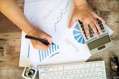 Geschäftsfrau, die einen Taschenrechner verwendet, um die Zahlen zu berechnen Stockfotografie