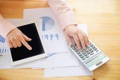 Geschäftsfrau, die einen Taschenrechner verwendet, um die Zahlen zu berechnen Stockfotos