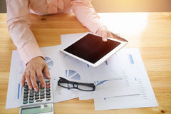 Geschäftsfrau, die einen Taschenrechner verwendet, um die Zahlen zu berechnen Lizenzfreies Stockfoto