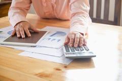 Geschäftsfrau, die einen Taschenrechner verwendet, um die Zahlen zu berechnen Lizenzfreies Stockbild