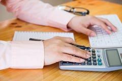 Geschäftsfrau, die einen Taschenrechner verwendet, um die Zahlen zu berechnen Lizenzfreie Stockfotografie