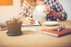 Geschäftsfrau, die einen Tasse Kaffee hält und Unternehmensplan schreibt Stockfoto