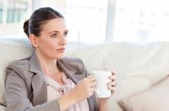 Geschäftsfrau, die einen Tasse Kaffee trinkt Stockfoto