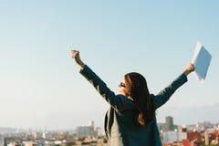 Geschäftsfrau, die Erfolg in Richtung zu den Stadtskylinen feiert Lizenzfreie Stockfotografie