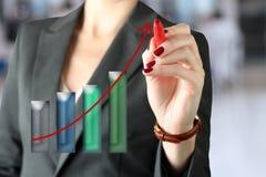 Geschäftsfrau, die etwas auf einem virtuellen Diagramm durch einen Stift zeigt Stockbilder