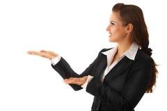 Geschäftsfrau, die etwas auf leeren Händen darstellt Stockbilder