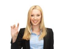 Geschäftsfrau, die etwas eingebildet hält stockfotos