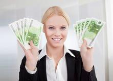 Geschäftsfrau, die Eurobargeldanmerkungen anhält Stockfoto