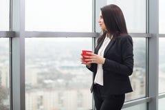 Geschäftsfrau, die am Fenster mit Schale steht Stockfoto