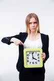 Geschäftsfrau, die Finger auf großer Uhr zeigt Lizenzfreies Stockfoto