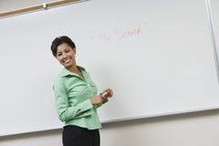 Geschäftsfrau, die in Front Of Whiteboard steht stockbild