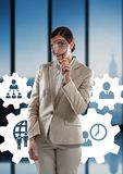 Geschäftsfrau, die gegen Leute in den Zahngraphiken gegen Bürohintergrund steht Stockfotografie