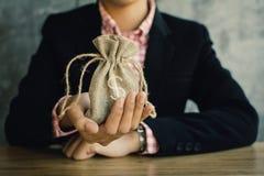 Geschäftsfrau, die Geld für die Rettung hält Stockbilder